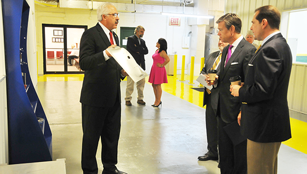 Matt Erskine (second from right) with the U.S. Economic Development Administration, listens to MT's Director of Marketing Mal McGhee talk about how the plant manufactures parts during a tour this morning. | Andrew Garner/Atmore Advance