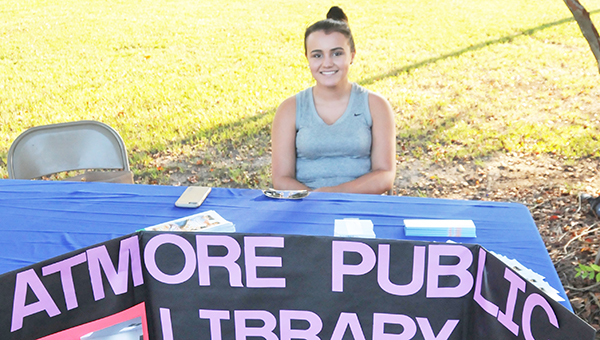 Sydnie Lassiter, daughter of Hope Lassiter who is the director of the Atmore Public Library, takes charge of the APL booth at the United Fund kick off last Thursday. | Andrew Garner/Atmore Advance