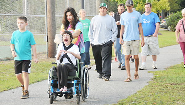 Mary Ellen Ray (far left) smiles as she is pushed around Tom Byrne Park's walking and running path Saturday night. | Andrew Garner/Atmore Advance