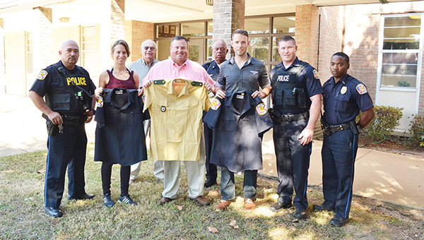 Two police officers from Germany were in town this week to exchange uniforms with the Atmore Police Department as a sign of appreciation. Shown above are Sgts. Janine Meier and  Theodor Fischer, along with Chief Chuck Brooks, holding the uniforms with APD patrol officers. | Andrew Garner/Atmore Advance