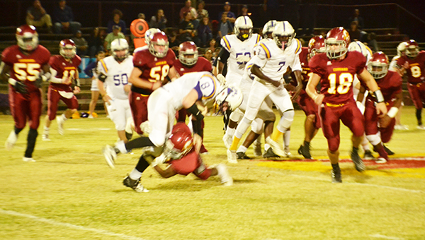 Escambia Academy's Fred Flavors (center) gets a tackle on Evangel Christian's Caleb Rigsby tonight. | Andrew Garner/Atmore Advance