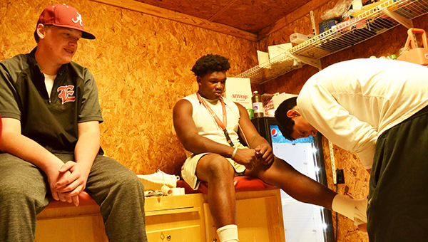 Escambia Academy athletic trainers Ben Martin (left) and Kevin Gumapac (right) have been assisting the football team all season. Both are shown working on getting tape off of Trae Lee's ankle Friday night. | Andrew Garner/Atmore Advance