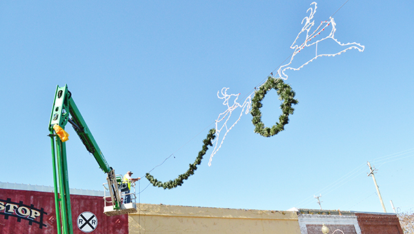 A city of Atmore employee hangs Christmas decorations above Main Street last week.                                          Andrew Garner/Atmore Advance