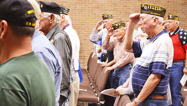 Veterans salute the flag during the city of Atmore's Veterans Day program Monday afternoon at city hall.   Andrew Garner/Atmore Advance